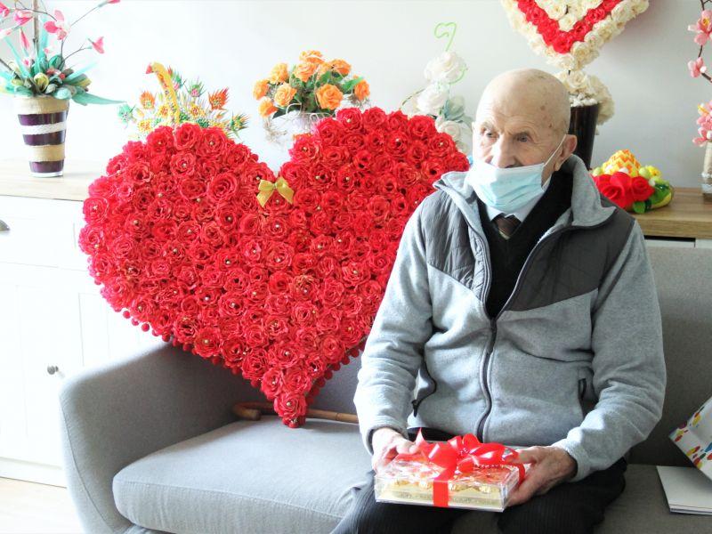 starszy mężczyzna w maseczce  siedzi na kanapie obok niego serce z bibułowych róż