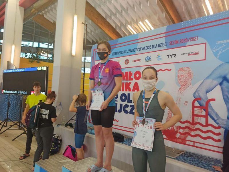 Na zdjęciu dwie zawodniczki na podium. Zawodniczki trzymają w ręku dyplomy i są udekorowane medalami. Z tyłu baner zawodów pływackich