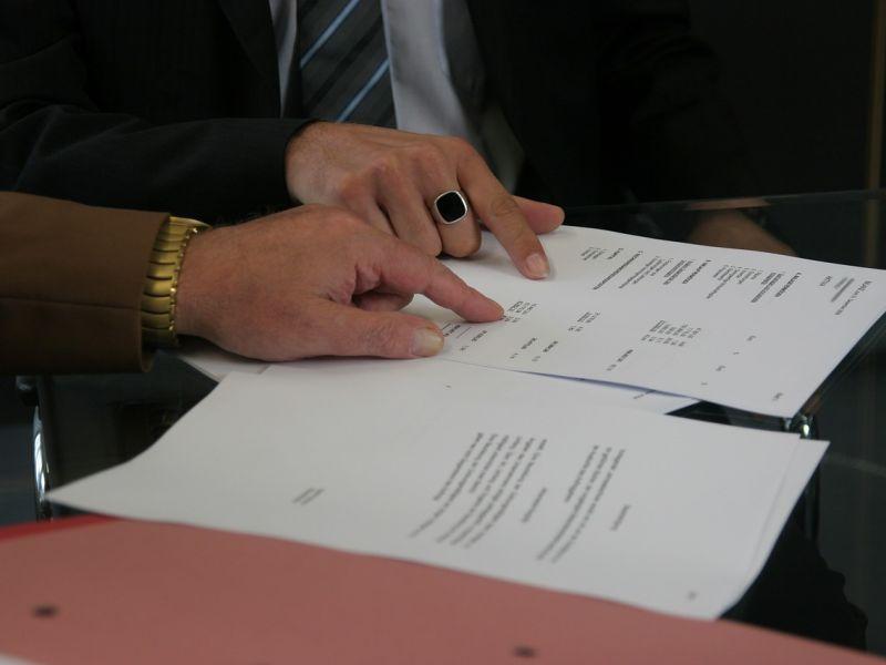 Na zdjęciu widać dwie kartki, dwie męskie dłonie wskazujące notatki