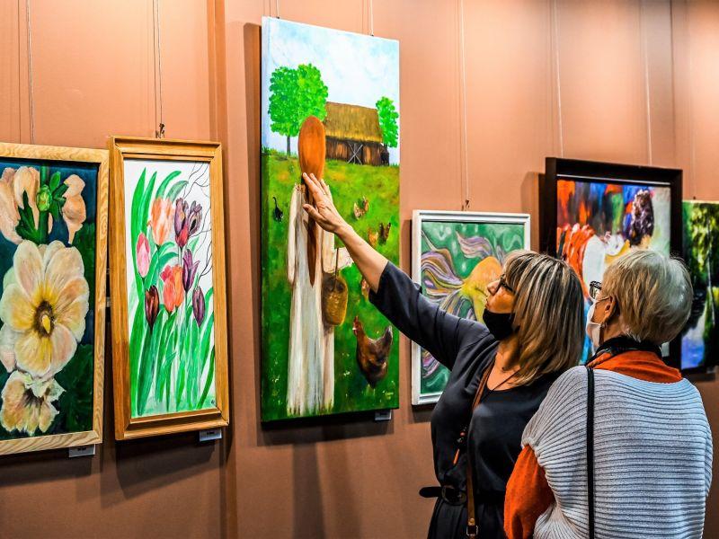 Na zdjęciu dwie kobiety oglądające obrazy zgromadzone na wystawie MCK. Jedna z kobiet pokazuje ręką na konkretny obraz