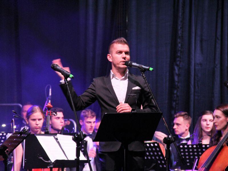Na zdjeciu Kamil Wrona instruktor MCK, stojący na scenie przed mikrofonem. W tle muzycy Młodzieżowej Orkiestry Symfonicznej Tomaszowa Mazowieckiego