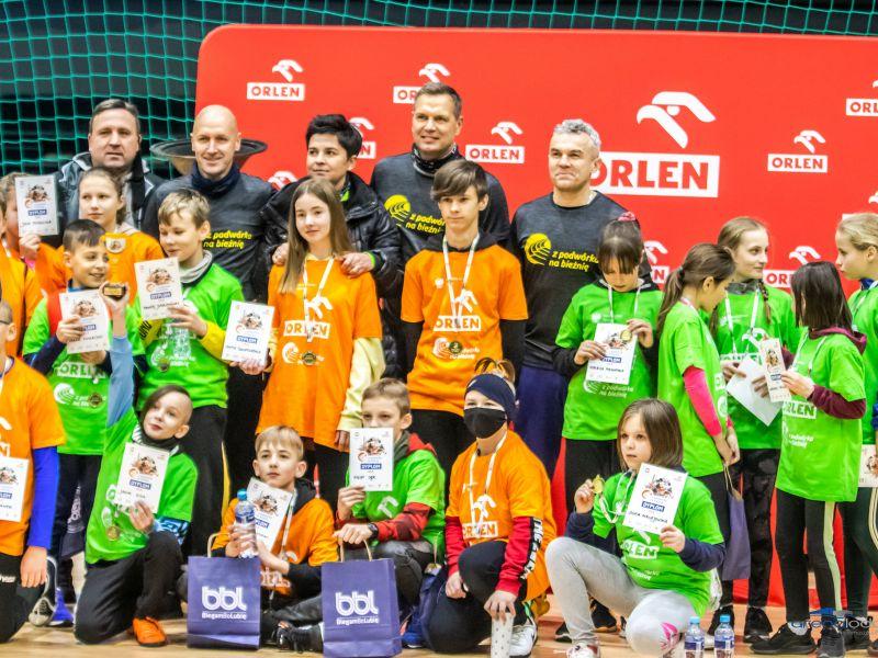 Na zdjęciu uczestnicy warsztató Z podwórka na bieżnię zorganizowanych w Arenie Lodowej. Zdjęcie grupowe wraz z olimpoijczykami, dzieci ubrane w koszulki sportowe, w rękach trzymają dyplomy, na piersiach medale okolicznościowe