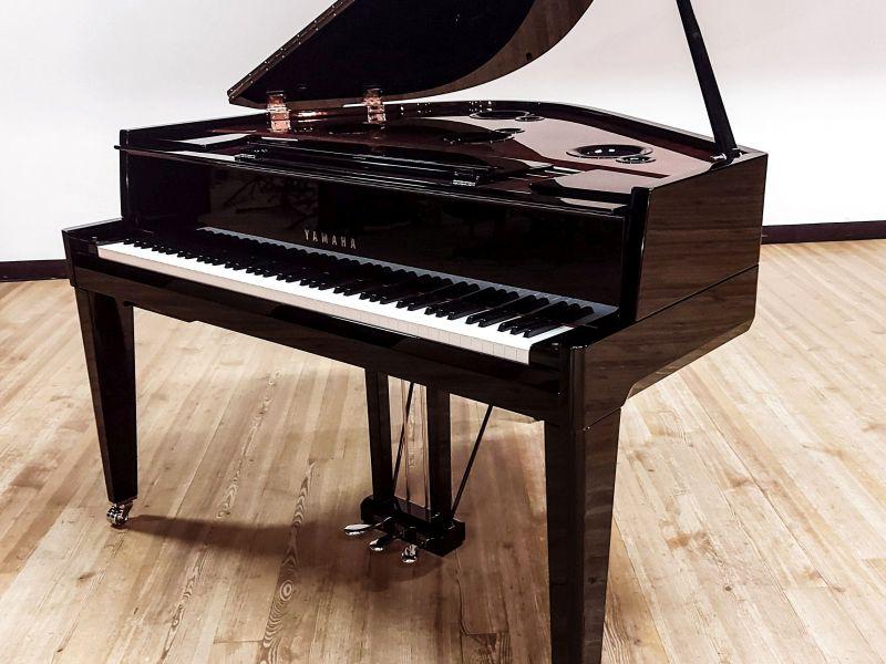 na zdjęciu widać brązowy fortepian na jasnym tle
