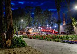 Na zdjęciu widać zrewitalizowany Park Bulwary. Zdjęcie przedstawia obiekt podświetlony nocą, na fotografii widac fragment chodnika sppacerowego, mostek nad rzeką Wolbórką i nasadzenia flory
