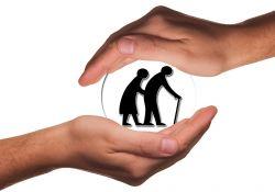 na białym tle dwie dłonie miedzy którymi jest przeźroczysta kula w której znajduje para starszych ludzi